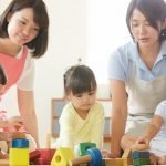 Daycare givers attending to infants as they learn with models in a childcare centre in Japan
