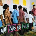 Indian school children (in a queue) having literacy skills lessons