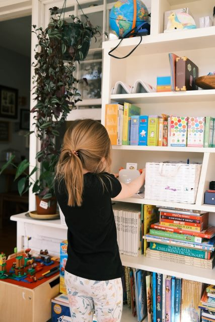 A girl accessing available books in a homeschool shelf