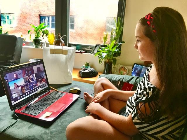 A girl comfortably learning at home through her laptop computer